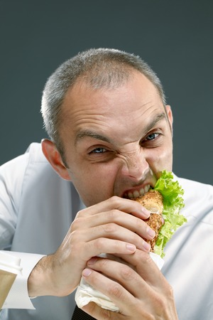 adult sandwich: Young man eating sandwich with pleasure Stock Photo