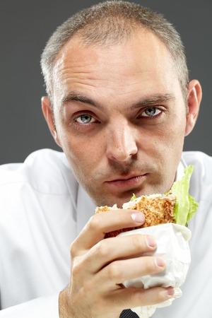 hombre comiendo: Hombre serio que come el emparedado Bckground gris