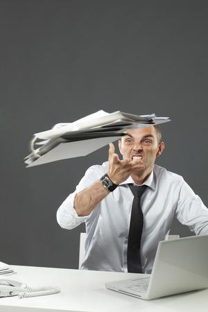 Furious businessman throwing his paper away