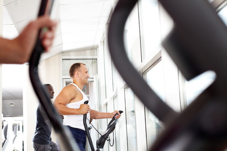 personas saludables: Two young men running on treadmill in gym