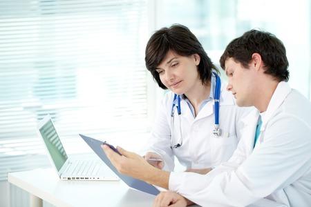 Dos doctores que examinan resultado de la prueba en oficina