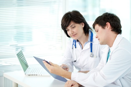 test result: Two doctors examining test result in office