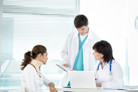 recommendations: Two doctors working with female patient in neck brace Stock Photo