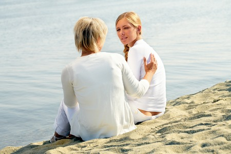 confide: Mother with daughter sitting near the water and talking