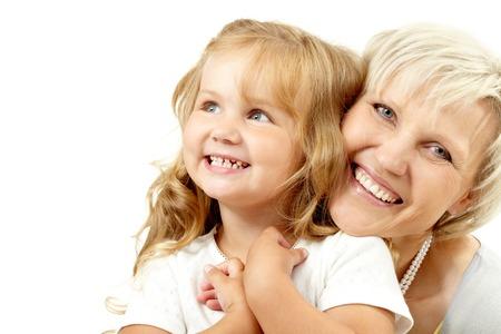 Šťastná babička objímá svou vnučku a dívá se na kameru