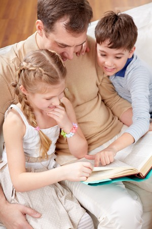 Father with children sitting at sofa and reading book photo