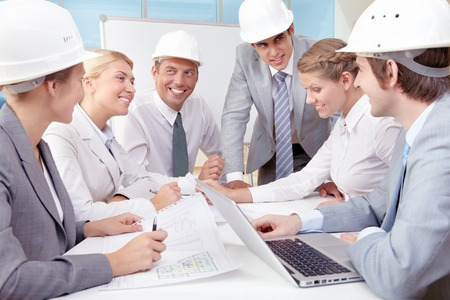 executive helmet: Group of young business people sitting at the table and discussing