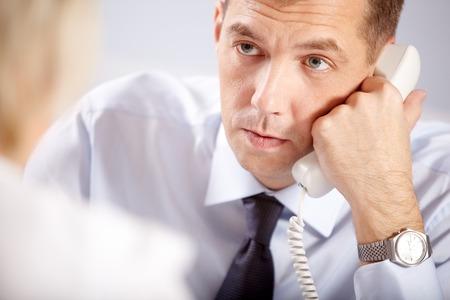 reunion de trabajo: hombre de negocios serio joven hablando por teléfono