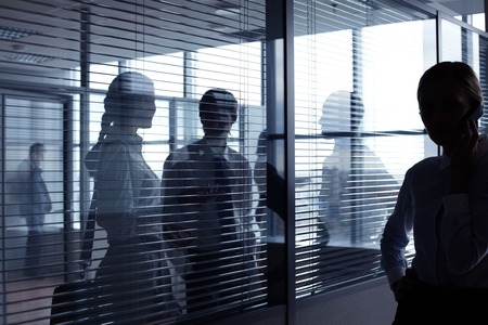 personas comunicandose: Unrecognizable business people communicating behind glass wall with blinds