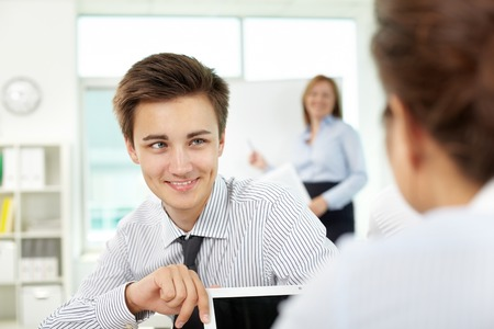 Young man flirting with his neighbor while woman giving a presentation Stock Photo