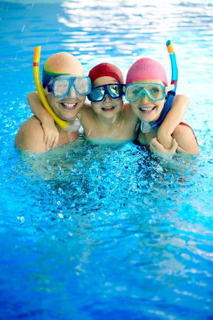Happy family in water wearing scuba mask looking at camera photo