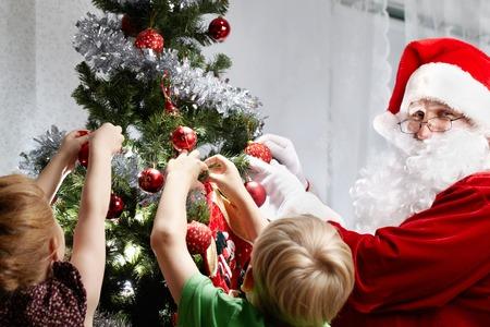 decorating christmas tree: Children with Santa Claus decorating a Christmas tree