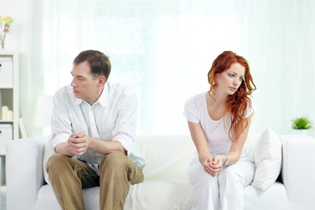 relationship difficulties: Young couple with relationship difficulties sitting on sofa at home
