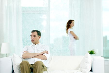 turn away: Displeased man sitting on sofa with arms crossed while his wife standing near the window Stock Photo