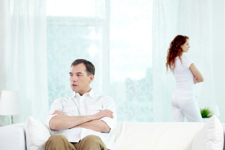 turn away: Man sitting on sofa with his wife standing on the background