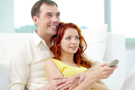 pareja viendo television: Smiling couple watching TV together at home