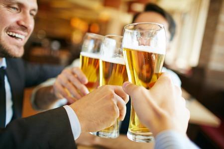 Los hombres de negocios que beben cerveza después de acuerdo exitoso