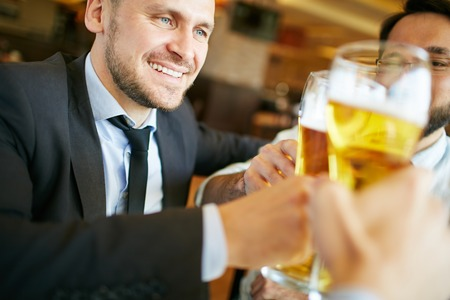 cheers: Businessman spending time with his friends drinking beer at pub