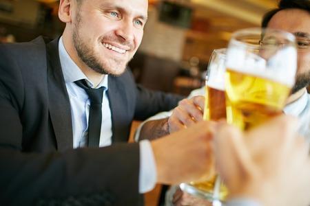 Zakenman tijd doorbrengen met zijn vrienden bier drinken in de pub