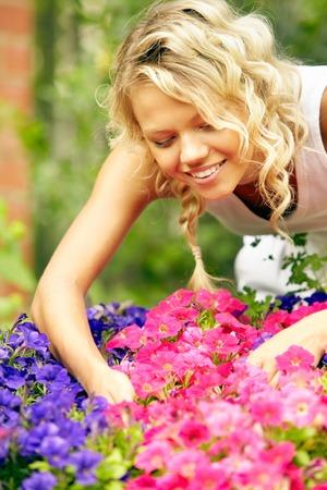 mooie vrouwen: Lachende jonge vrouw de zorg over bloemen