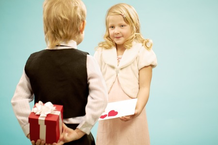 Beautiful girl giving a greeting card to boy while he hiding a present for her Stock Photo