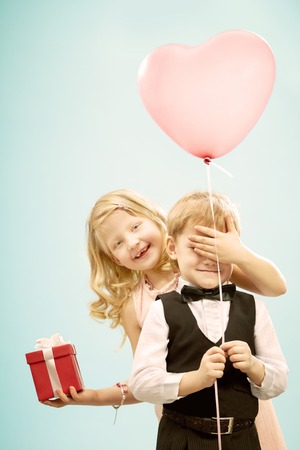 Pretty little girl covering boy s eyes and holding present for him