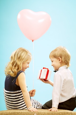 Little cute girl sitting with balloon with little boy giving a gift to her