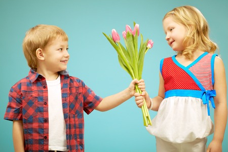 Cute little boy giving flowers to pretty little girl