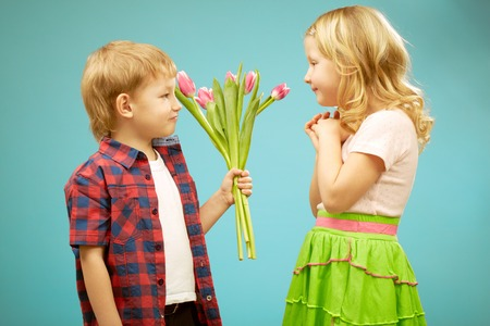 confessing: Blond hair boy giving flowers to cute blond hair girl on blue background Stock Photo