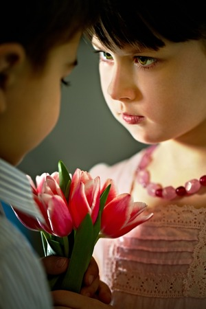 Pretty girl giving flowers to boy Stock Photo