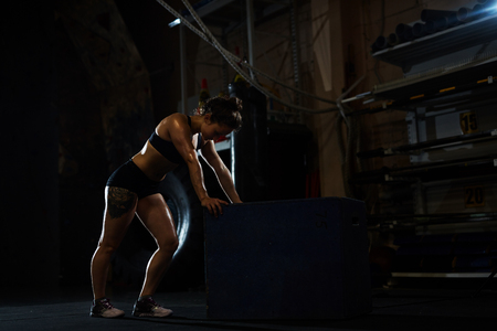 exercise: Young woman standing at jump box in gym Stock Photo