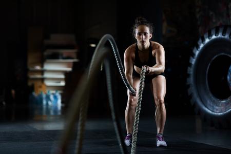 Junge Frau, die Schlacht Seil Übungen im Fitness-Studio Standard-Bild - 63442494