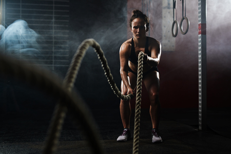 Young sporty woman pulling ropes at gym