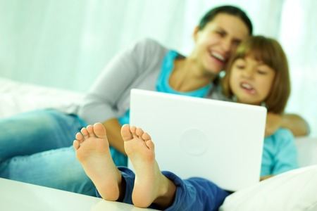 girl using laptop: Happy mother and daughter sitting on sofa with laptop