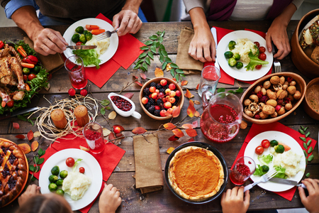 Por encima de vista de la cena de Acción de Gracias y la familia comiendo en la mesa