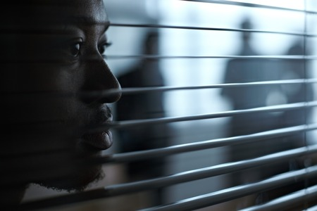 blinds: Serious African businessman against blinds