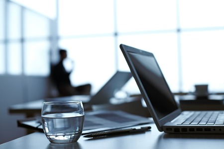 glass table: Laptop, pen and glass of water on the table with businessman working on background Stock Photo