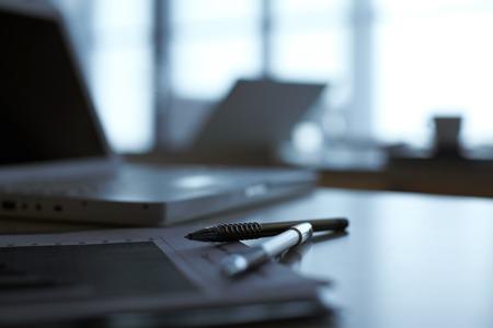 Een notitieboekje en pennen op tafel met laptop op de achtergrond liggen Stockfoto