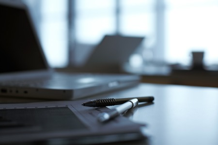 Ein Notizbuch und Stifte, die auf Tabelle mit Laptop auf Hintergrund liegen Standard-Bild