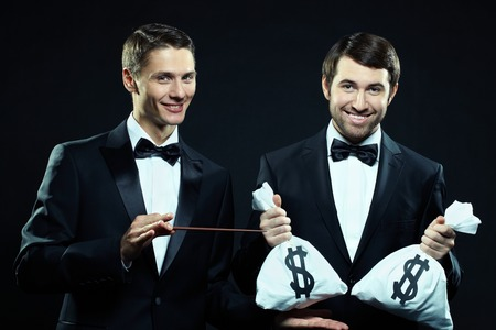 croupier: Portrait of two men in tuxedoes holding sacks with money and pointing at them