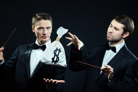 conjuring: Two men in tuxedoes conjuring over sack of money Stock Photo
