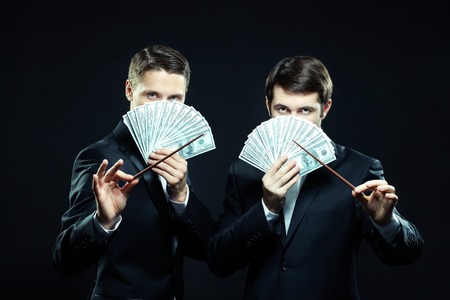 swindler: Portrait of two men in tuxedoes with dollar banknotes and wands