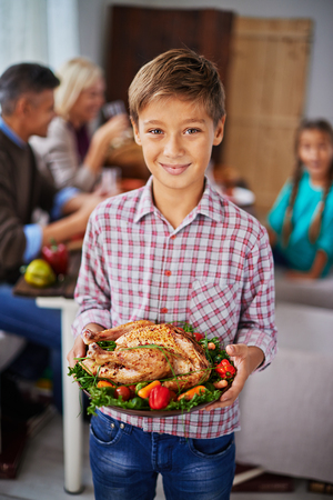 Portrait of teenage boy holding thanksgiving turkey and smiling at camera photo