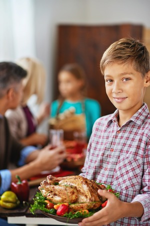 Smiling boy holding thanksgiving poultry, his family eating in the background photo