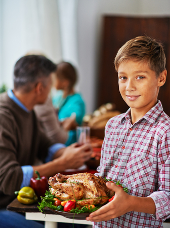 Boy posing with roasted chicken with his family in the background Stock Photo