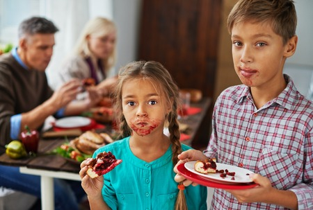 Boy and girl eating sweet pie with dirty mouths, their parents eating in the background photo