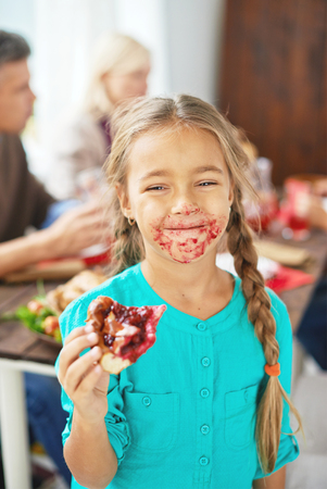 Portarit of a little girl with eating a pie and smiling at camera with smudgy mouth with her family in the background Stock Photo