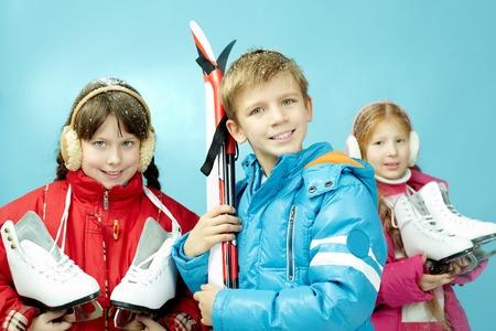 niño en patines: Retrato de niñas con los patines y un niño con los esquís aislado en azul Foto de archivo