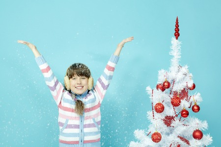 arms up: Portrait of little girl standing by Christmas tree and rejoicing