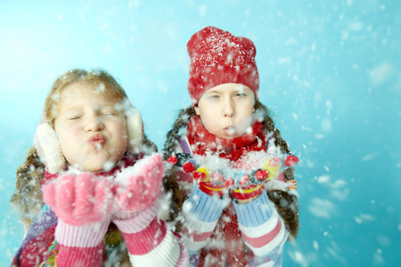 Portrait of two little girls blowing snow at camera Stock Photo